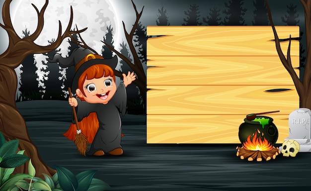 Heureux enfant portant le costume de sorcière se tenir à côté de la planche de bois