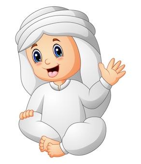 Heureux enfant vêtu de vêtements arabes, agitant la main