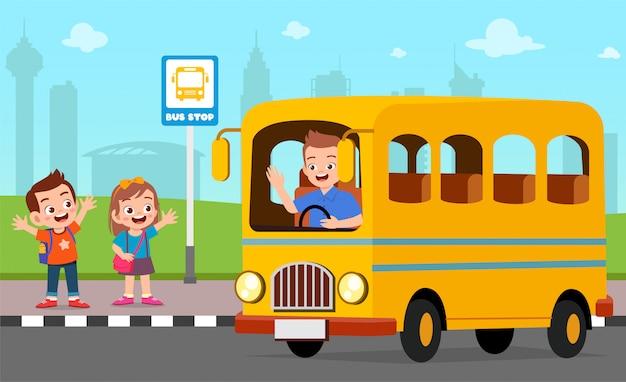 Heureux enfants mignons attendent le bus scolaire avec des amis