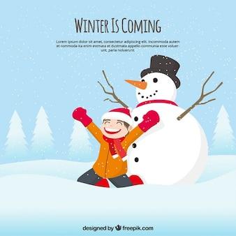 Heureux fond de l'enfant dans un paysage enneigé avec bonhomme de neige