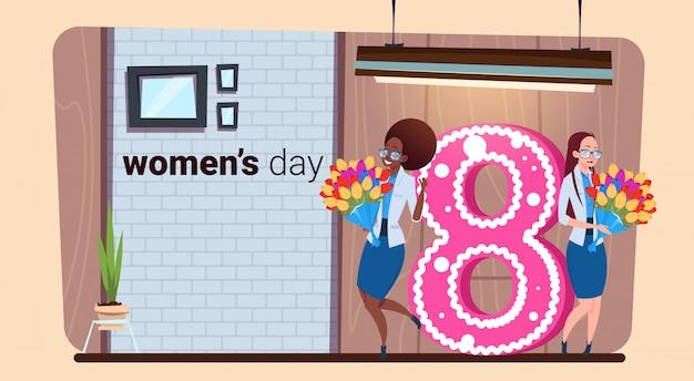 Heureux fond de la journée internationale des femmes avec deux filles tenant une carte de voeux créative de fleurs 8 mars vacances