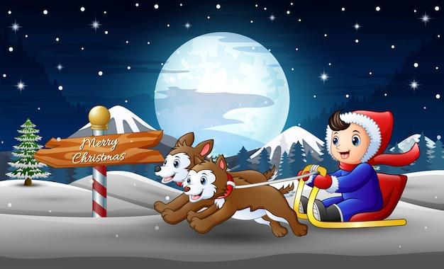 Heureux garçon à cheval sur un traîneau tiré par deux chiens la nuit d'hiver