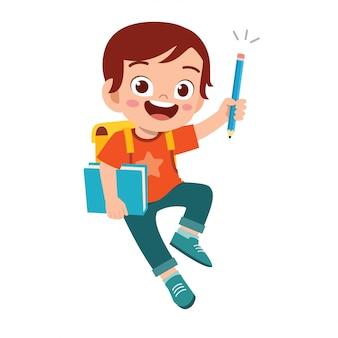 Heureux garçon enfant étudiant mignon avec livre et crayon