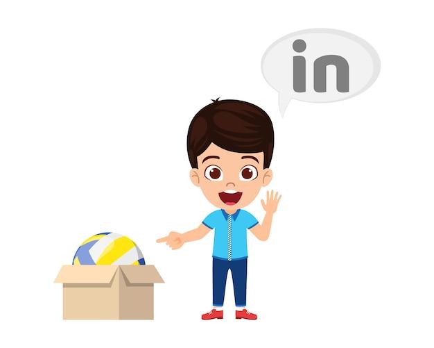 Heureux garçon enfant mignon avec ballon et carton, apprentissage du concept de préposition, en préposition et pointage