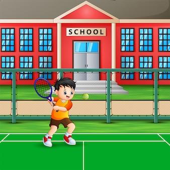Heureux garçon jouant au tennis à la cour de l'école