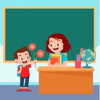 Heureux garçon mignon donne des fleurs au professeur