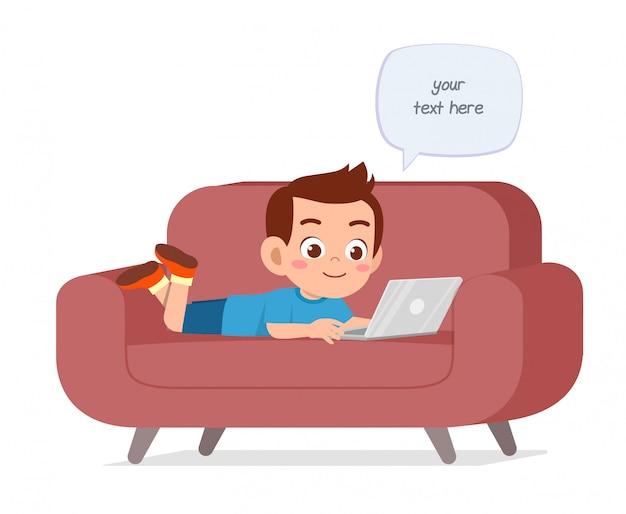 Heureux garçon mignon enfant utilise un ordinateur portable sur le canapé