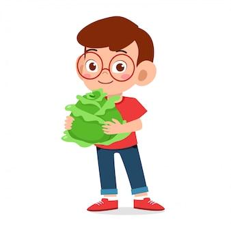 Heureux garçon mignon tenant des légumes frais