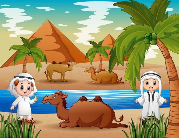 Heureux garçons arabes avec des chameaux dans le désert
