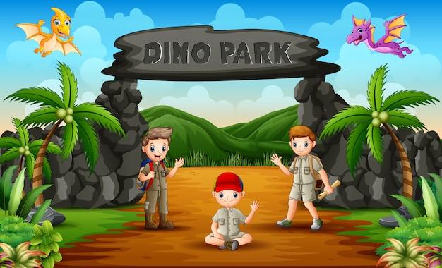 Heureux les garçons de l'explorateur agitant dans le parc des dinosaures