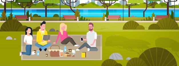 Heureux gens ayant pique-nique dans le parc groupe de jeunes hommes et femmes assis sur l'herbe se détendre et communiquer