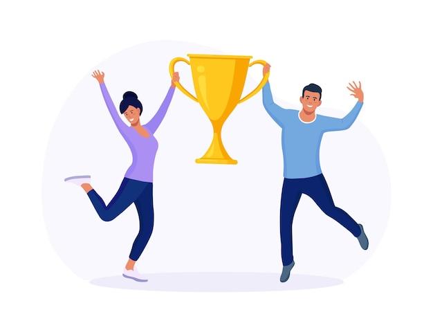 Heureux homme et femme tenant le gobelet d'or. gagnants célébrant la victoire. hommes d'affaires avec prix, golden trophy cup. les gens qui réussissent gagnent un prix. célébration du succès de l'équipe commerciale, réalisation des objectifs