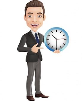 Heureux jeune homme d'affaires tenant et pointant une horloge murale