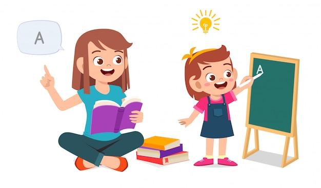 Heureux mignon petit enfant fille étude avec maman