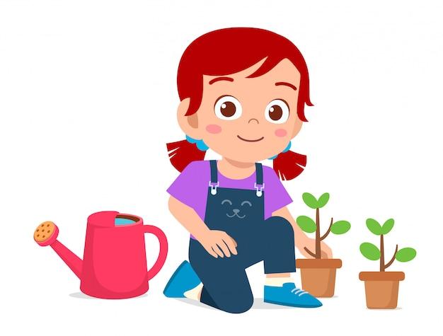 Heureux mignon petit enfant fille plante arbre dans le jardin