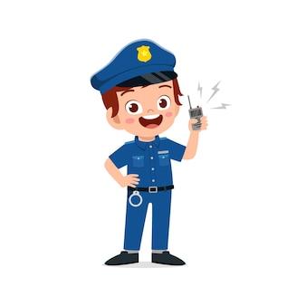 Heureux mignon petit garçon enfant portant l'uniforme de la police
