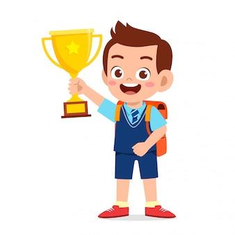 Heureux mignon petit garçon enfant tenant le trophée