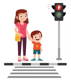 Heureux mignon petit garçon enfant traverser la route avec la mère