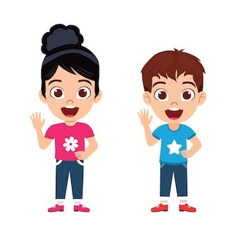 Heureux mignon petit garçon et fille debout avec une expression joyeuse et en agitant et isolé