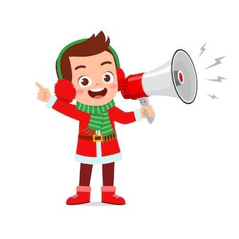 Heureux mignon petit garçon et fille portant un costume de noël rouge et tenant un mégaphone