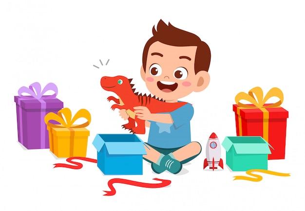 Heureux mignon petit garçon garçon ouvert cadeau d'anniversaire