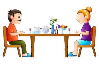 Heureux père et mère de dessin animé, manger sur la table à manger