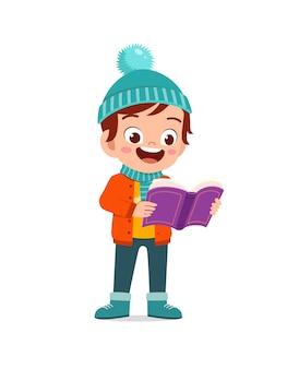 Heureux petit enfant mignon étudie et porte une veste en hiver