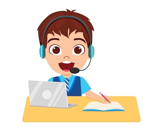 Heureux petit enfant mignon faire l'école à domicile avec ordinateur portable se connecter à internet étude elearning et cours isolé sur fond blanc et casque et écriture