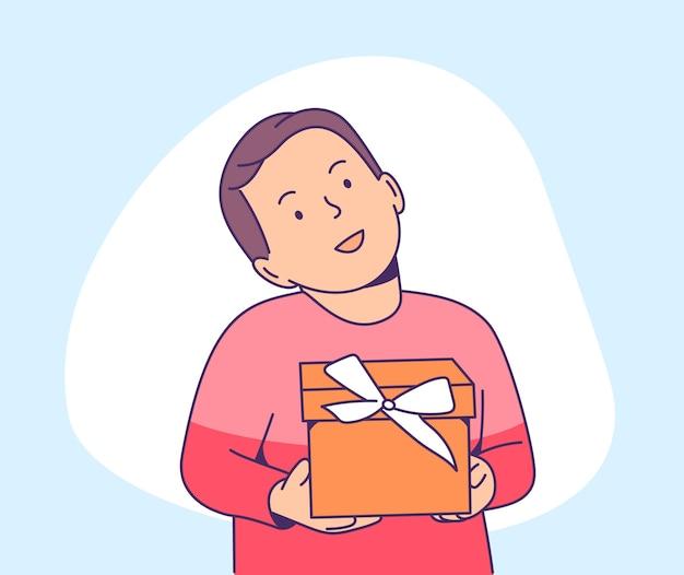 Heureux petit enfant tenant une boîte cadeau