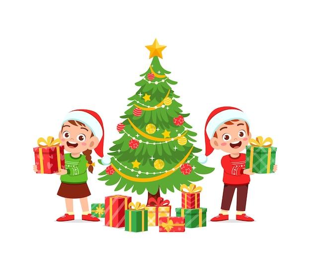 Heureux petit garçon et fille tenant un cadeau pour noël