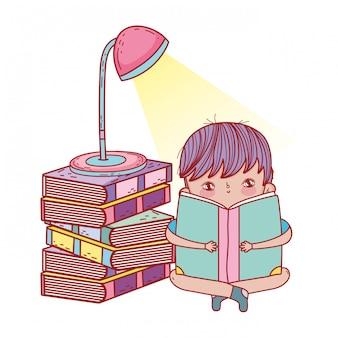 Heureux petit garçon lisant des livres avec lampe
