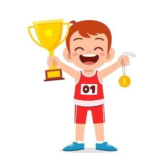 Heureux Petit Garçon Mignon Tenant Une Médaille D'or Et Un Trophée Vecteur Premium
