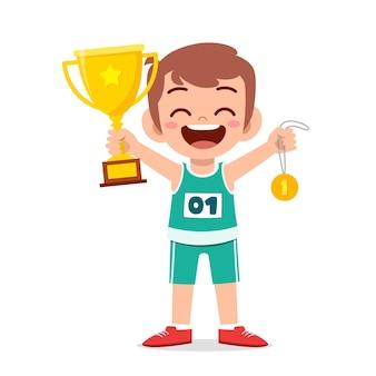 Heureux petit garçon mignon tenant une médaille d'or et un trophée