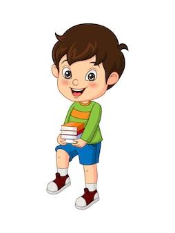 Heureux petit garçon mignon tenant une pile de livres