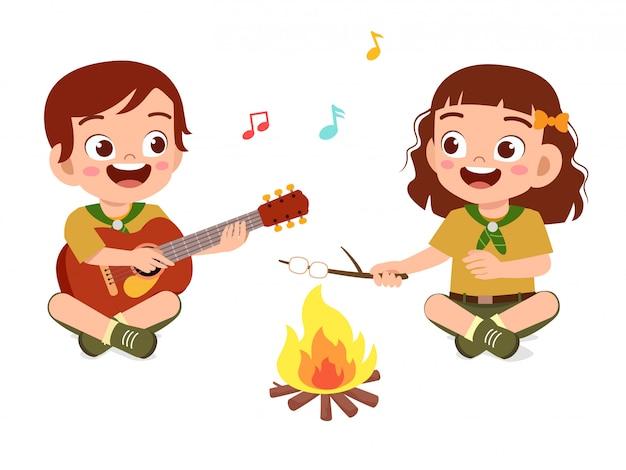 Heureux petit garçon scout mignon et fille chantent sur un feu de camp