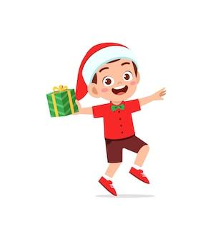 Heureux petit garçon tenant un cadeau pour noël