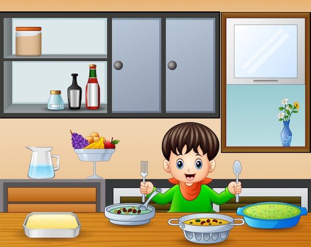 Heureux petit garçon tenant une cuillère et une fourchette à manger à la table