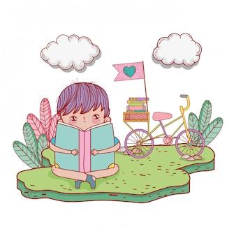 Heureux petit livre de lecture de garçon à vélo dans le champ