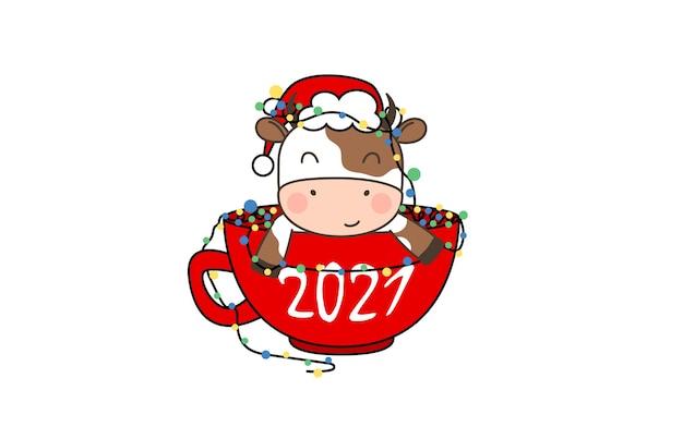 Heureux petit taureau mignon en bonnet de noel assis dans une tasse de café avec guirlande