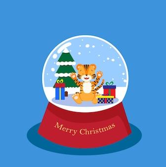 Heureux petit tigre dans une boule de verre enneigée avec de l'épinette