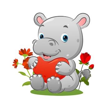 L'hippopotame mignon est assis sur l'herbe et tient le ballon coeur dans le jardin de l'illustration