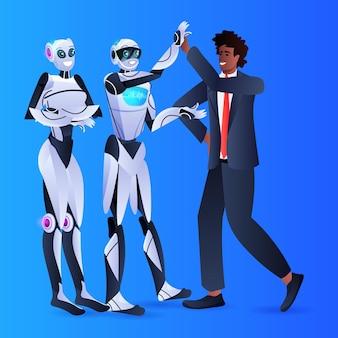 Homme d'affaires afro-américain et robots se donnant cinq hauts lors de la réunion d'accord de partenariat concept de technologie d'intelligence artificielle pleine longueur