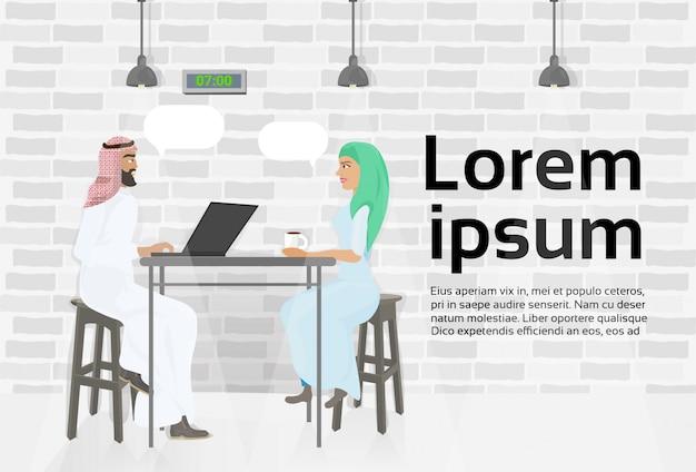 Homme d'affaires arabe et femme réunis dans le centre de coworking moderne travaillant à l'ordinateur portable. modèle de texte