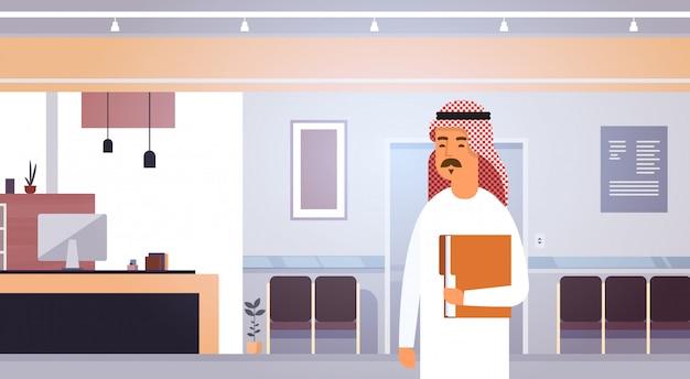 Homme d'affaires arabe tenant un dossier avec des documents entrepreneur dans un bureau moderne