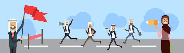Homme d'affaires arabe traversant la ligne d'arrivée porter le costume de bureau drapeau leader en position de bande de course fond isolé
