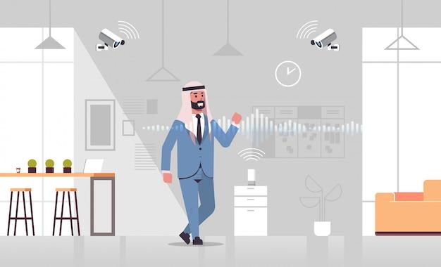 Homme d'affaires arabe utilisant une caméra de vidéosurveillance contrôlée par la reconnaissance vocale du haut-parleur intelligent