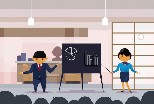 Homme d'affaires asiatique et femme tenant la présentation