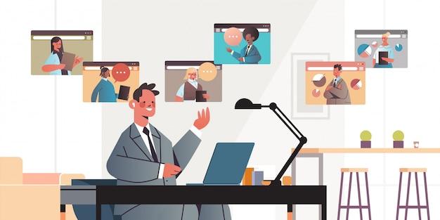 Homme affaires, bavarder, à, mélange, race, collègues, pendant, appel vidéo, gens affaires, avoir, conférence ligne, réunion, communication, concept, bureau, intérieur, portrait horizontal
