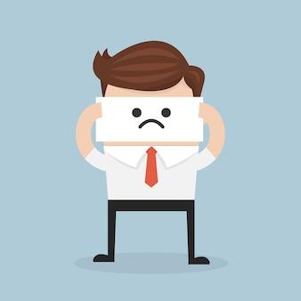 Homme d'affaires cache son vrai visage en tenant un masque de mauvaise humeur