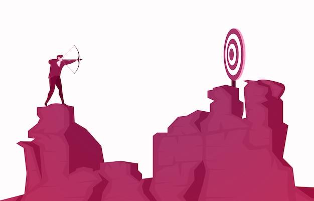 Homme d'affaires, debout sur la falaise, visant la cible de succès avec la flèche